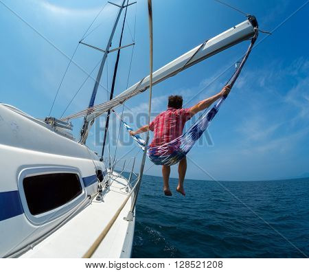 Man sits in the hammock set on the sail boat