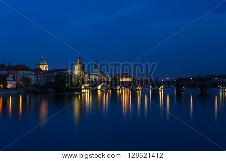 Prague city at blue night Charles Bridge reflection in Vltava river. Prague Czech Republic
