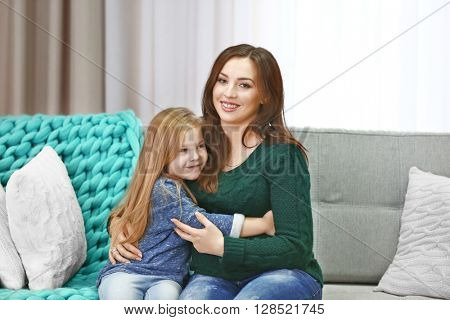 Happy pregnant woman and her child on couch