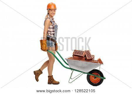 Female construction worker pushing a wheelbarrow full of bricks isolated on white background