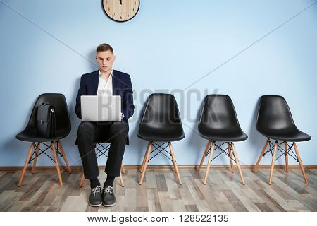 Young man in suit sitting on chair with laptop and waiting for job interview against blue wall background