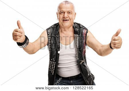 Mature man in an old punk leather jacket with pins giving thumbs up isolated on white background