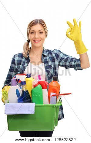 Vertical shot of a young housewife holding a bunch of cleaning equipment and making ok sign isolated on white background