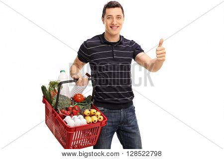 Cheerful young guy carrying groceries and giving a thumb up isolated on white background
