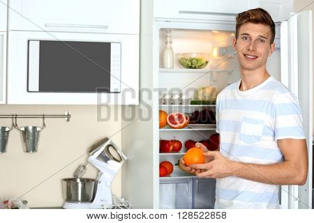 Handsome man taking food from refrigerator