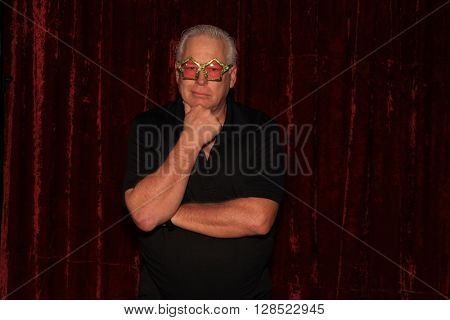 A handsome middle aged man laughs, smiles, and poses with crazy props while he has his pictures taken while in a photo booth. Photo Booths are very popular at all parties and weddings.