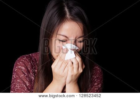 young asian woman blowing her nose with paper tissue