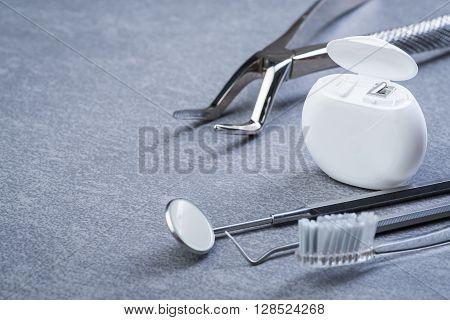 Basic Dental Tools, Floss And Brush On Grey Surface