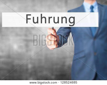 Fuhrung (leadership In German) - Businessman Hand Holding Sign