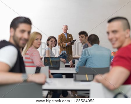 group of students study with senior professor in modern school classroom on creative class