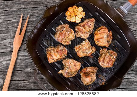 Hot delicious pieces of grilled meat on a skillet on a rustic table top view