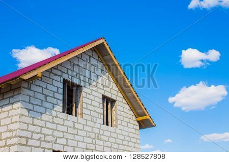 house under construction from aerated concrete blocks. unfinished house with a red roof against the blue sky and clouds. copy space for your text
