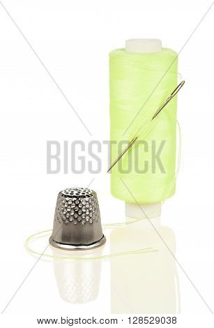 Coil with yellow thread needle and thimble isolated on white background