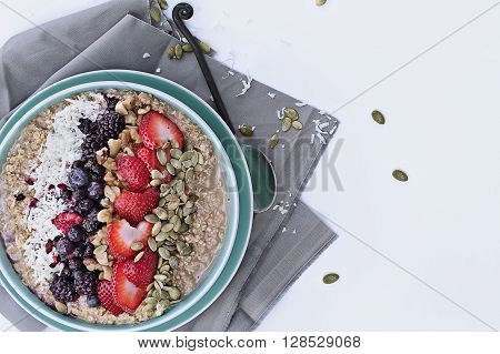 Hot breakfast of healthy oatmeal with shredded coconut blackberries blueberries walnuts heart shaped strawberries and pumpkin seeds over a white background. Image shot from overhead.