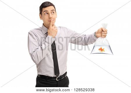 Young man holding a goldfish in a plastic bag with water and making a wish isolated on white background