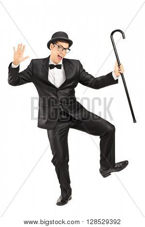 Full length portrait of a young male comedian dancing with a cane isolated on white background