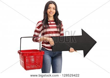 Young woman holding an empty shopping basket and an arrow pointing right isolated on white background
