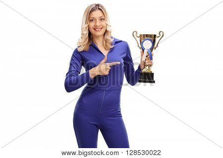 Young woman in a blue racing suit holding a trophy and pointing towards it isolated on white background