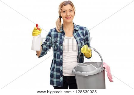 Cheerful woman holding a cleaning spray and a plastic bucker isolated on white background