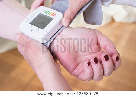 female doctor is showing a female patient how to use a blood pressure measurement device