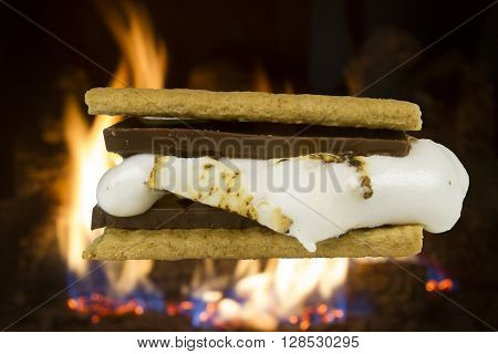 Chocolate s'more made from graham crackers chocolate bar and melting marshmallow in front of roaring campfire