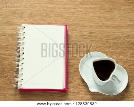 Heart shape of cup with coffee and heart shape of plate with opened book for diary. Love coffee. Top view. Happy Valentines Day background.