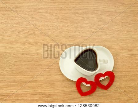 Heart shape of cup with coffee and heart shape of plate with two red hearts. Love coffee. Top view. Happy Valentines Day background.