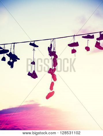 Vintage Toned Silhouettes Of Shoes Hanging On Cable At Sunset.