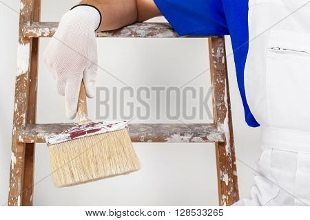 Painter In White Dungarees, Gloves And Paint Brush