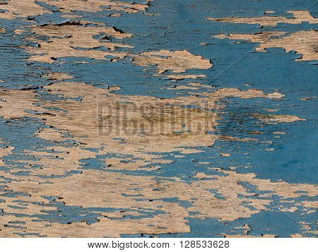 Full frame image of blue paint peeling to reveal wood underneath.