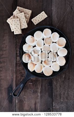 Smores dip in an old cast iron pan with ingredients over a rustic wooden background.