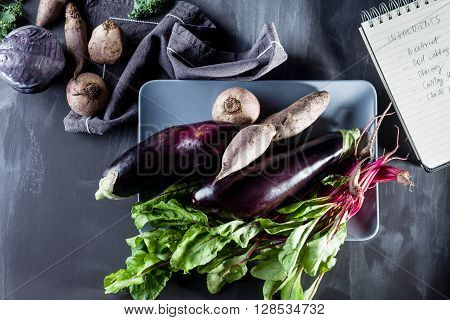 Beetroots aubergines and beet leaves on the plate with recipes notebook on the side top view