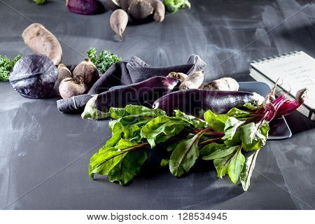 Beetroots aubergines and beet leaves on the plate with black notebook and cloth on the side