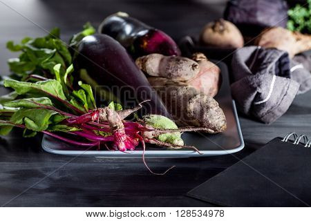 Beetroots aubergines and beet leaves on the plate with black notebook on the side