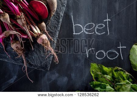 Bunch of beetroots on the stone and blackboard with chalk notes