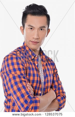 A confident young businessman stands with arms folded
