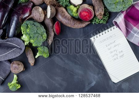 Beetroots curly kale broccoli and black turnip with cloth lying on blackboard with notebook with recipe