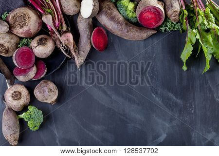 Beetroots curly kale broccoli and black turnip on the plate with knife lying on blackboard