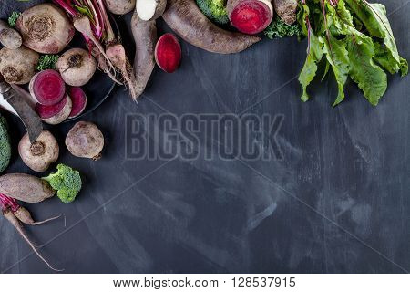 Beetroots curly kale broccoli and black turnip on the plate with knife lying on blackboard from the top