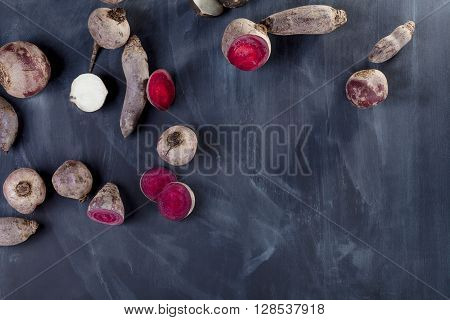 Beetroots and sliced turnip on blackboard from the top