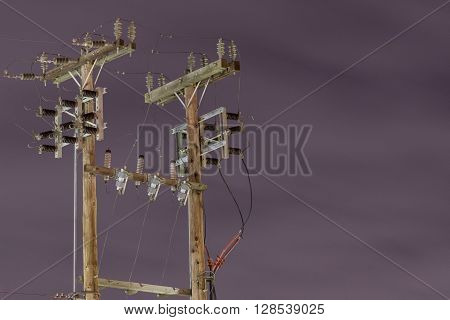 Power lines poles under hazy sky at night.