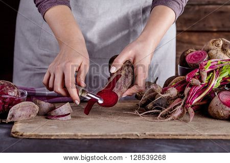 ook in gray apron is peeling a beetroot with vegetable peeler