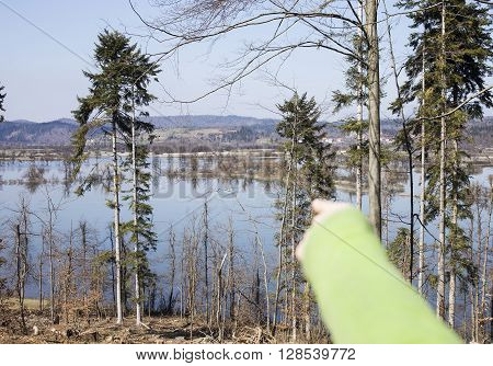 Pointing hand to flooded land by accumulation lake.