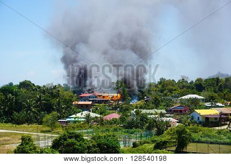 Labuan,Malaysia - Feb 27, 2016: Smoke rising from a raging fire in the village people house at Bukit Kuda village, Labuan on 27th Feb 2016