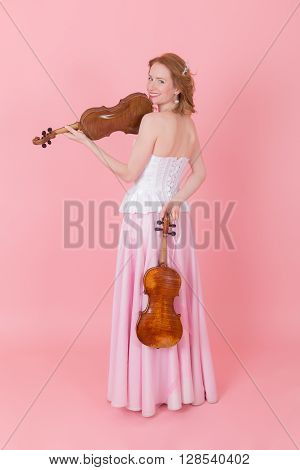 girl with a violin and viola on pink background