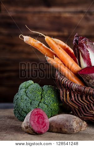 Basket full of healthy vegetables like carrots beetroot chicory broccoli whith wooden background