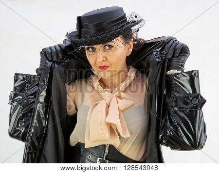Woman wearing a hat lifting the collar of a black PVC mac.