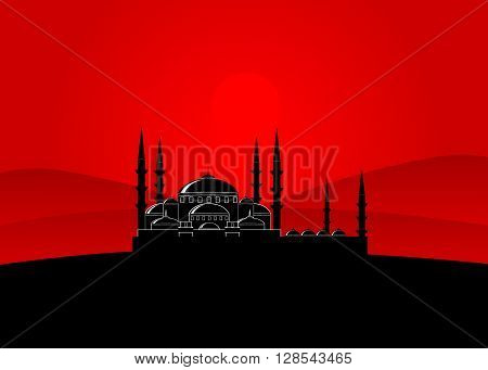 mosque. A mosque silhouette against the red sky and mountains