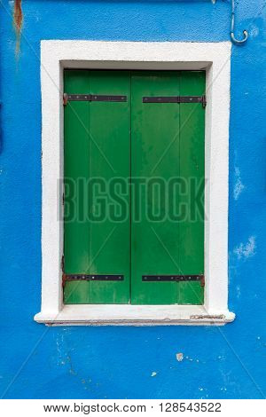 Picturesque old window with green shutters on blue wall (Burano island Venice Italy)