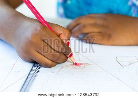 Close up of African kid's hand creating drawing on paper.
